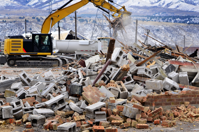 Heavy machinery clearing demolished building debris