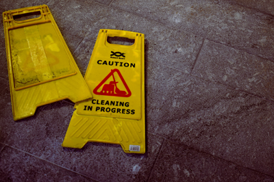 Wet floor with knocked-over caution sign