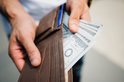 Hands holding money in a wallet
