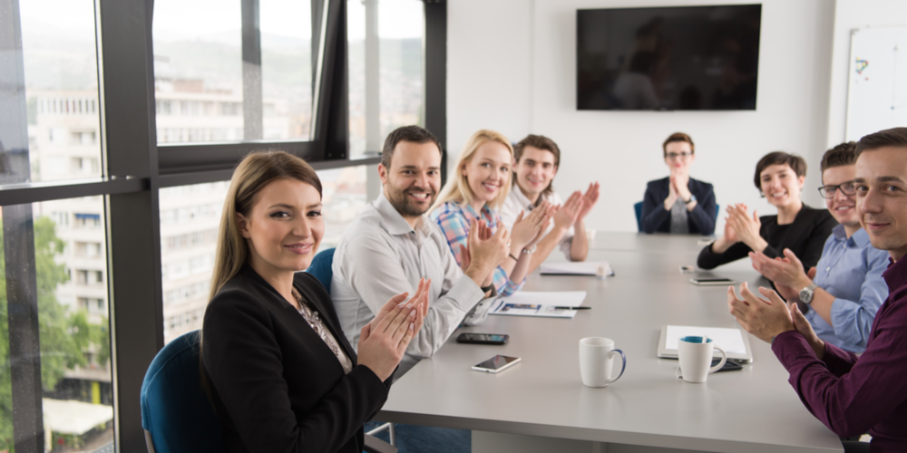 Professionals clapping hands at board meeting