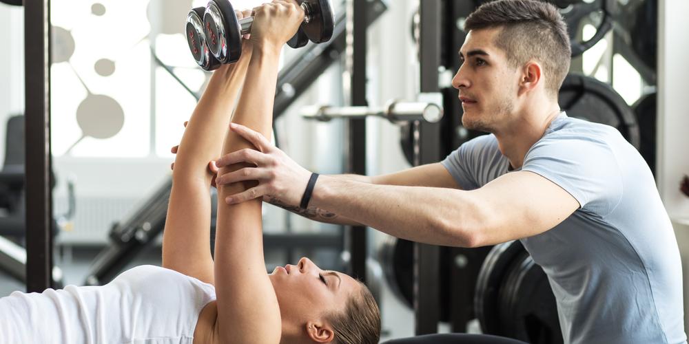 Man and woman lifting weights