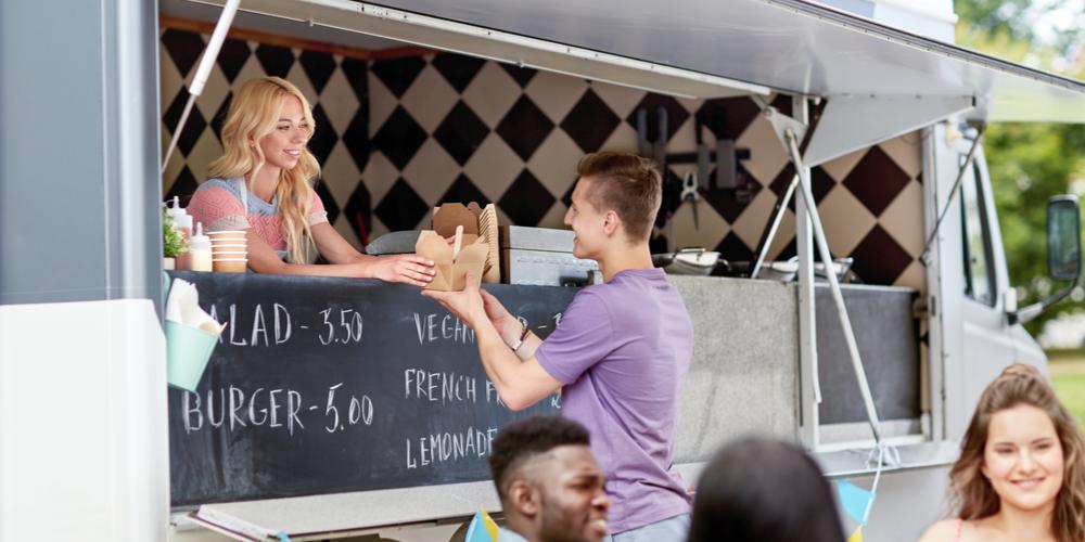 Woman giving man food order at food truck counter