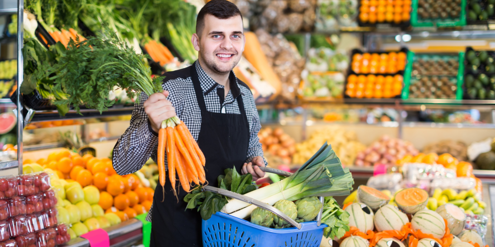 Grocery store attendant picking out produce
