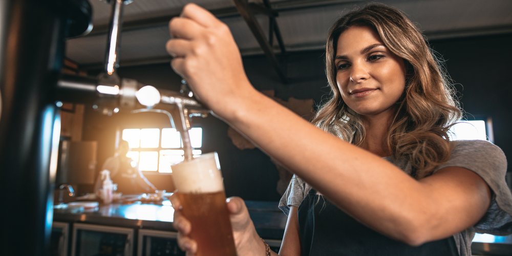 Woman pouring beer from tap at brewery