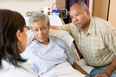 A patient and a loved one speaking with a doctor