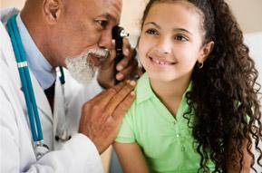Doctor checking little girl's ear