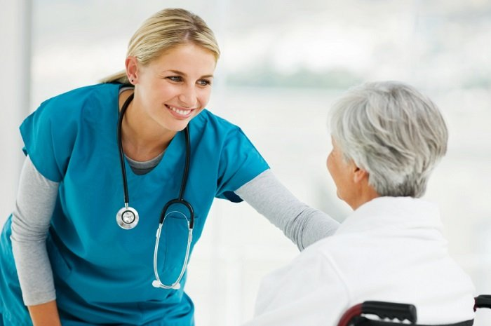 nurse smiling at patient in wheelchair