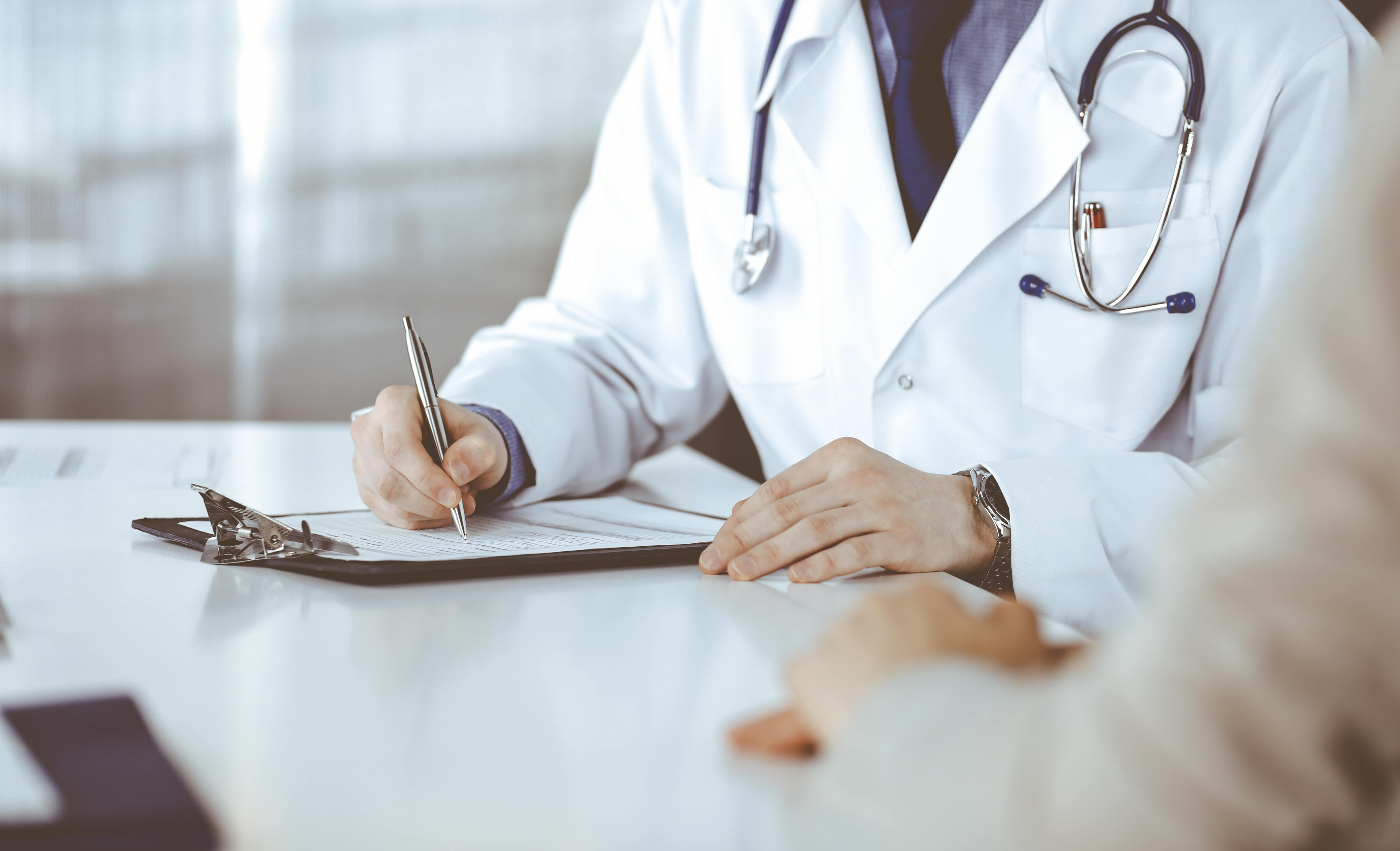 Doctor in white coat signing medical malpractice insurance paperwork
