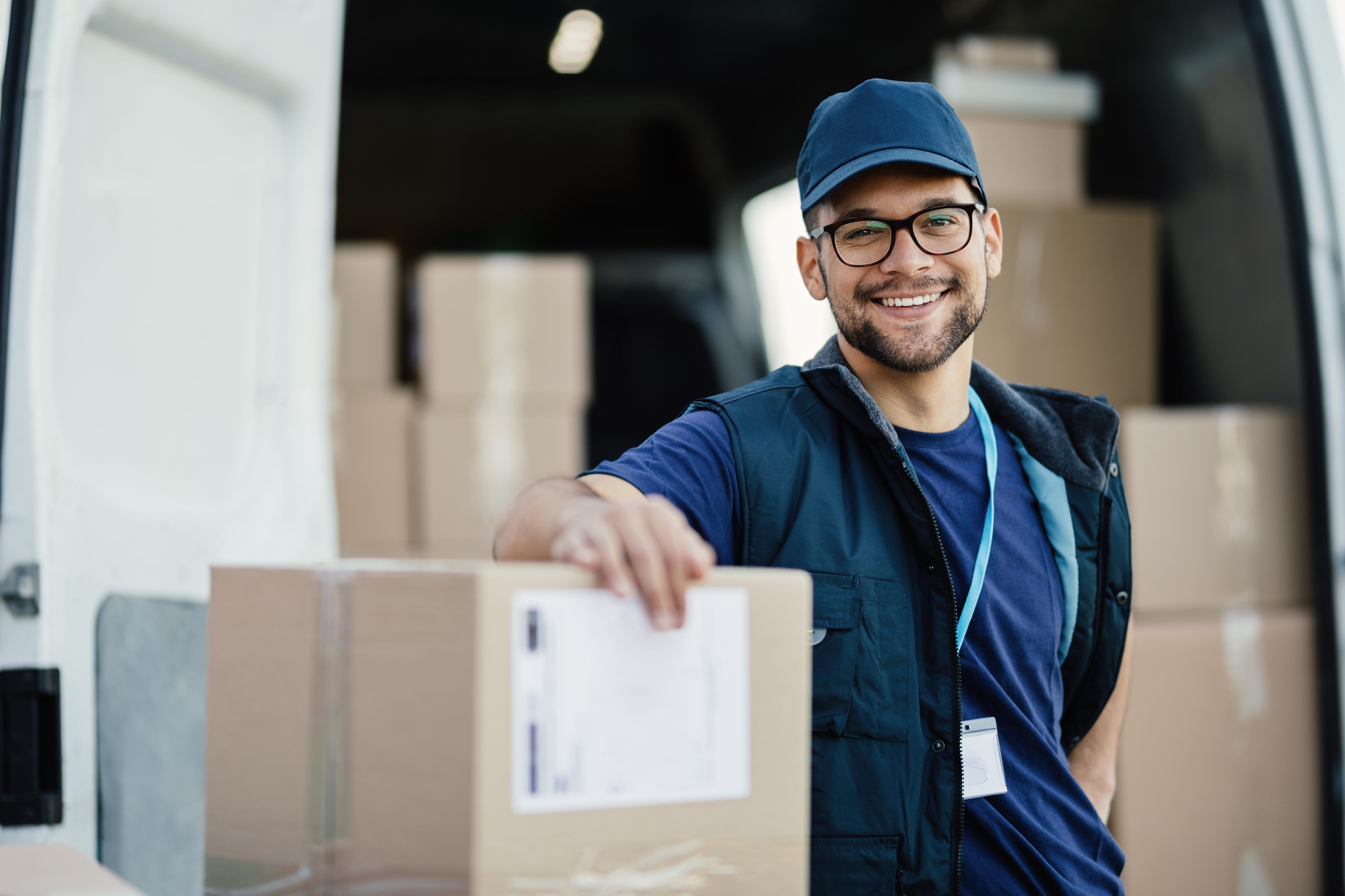 Delivery man smiling with boxes