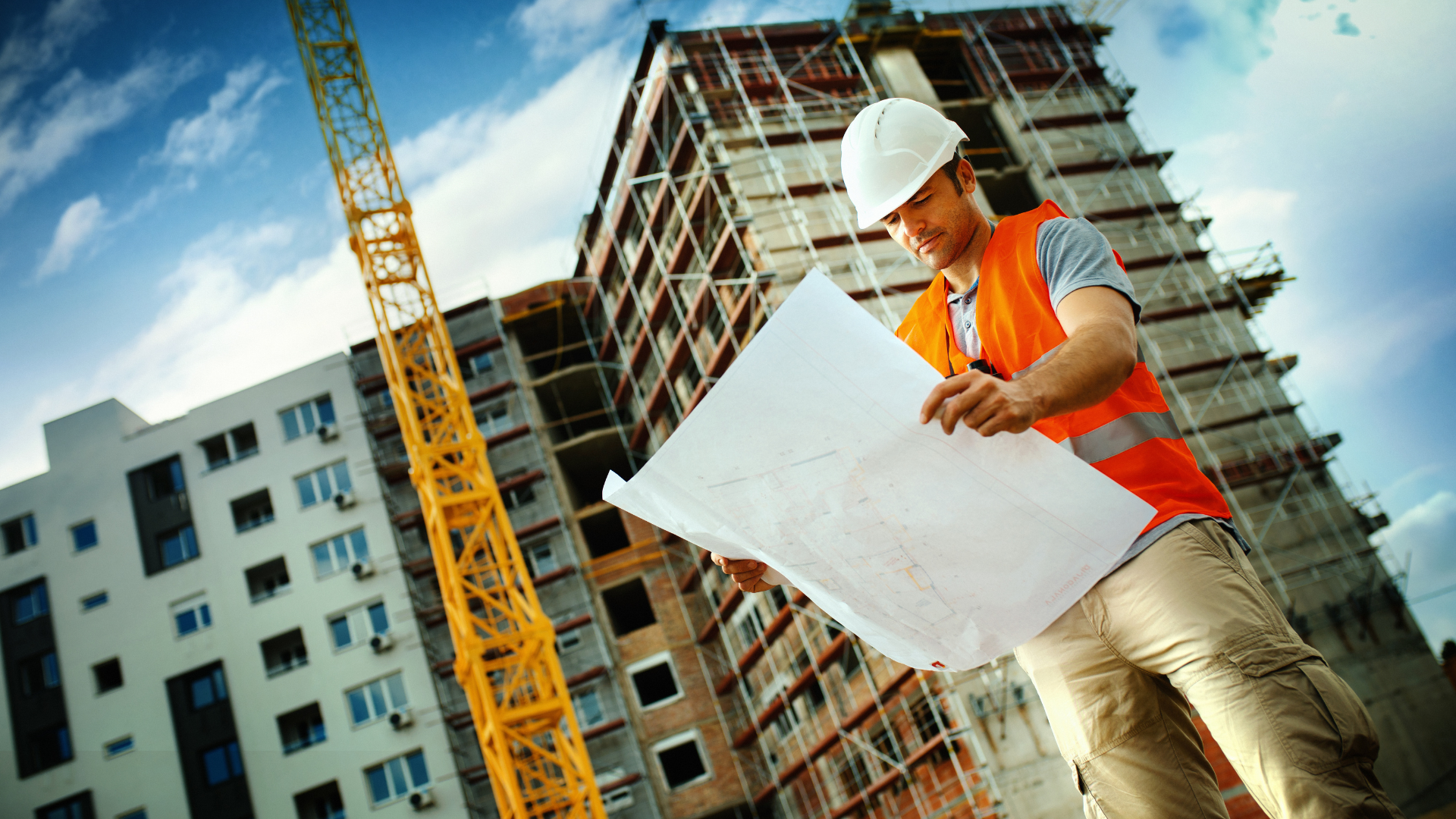 Contractor holding plans with building in background