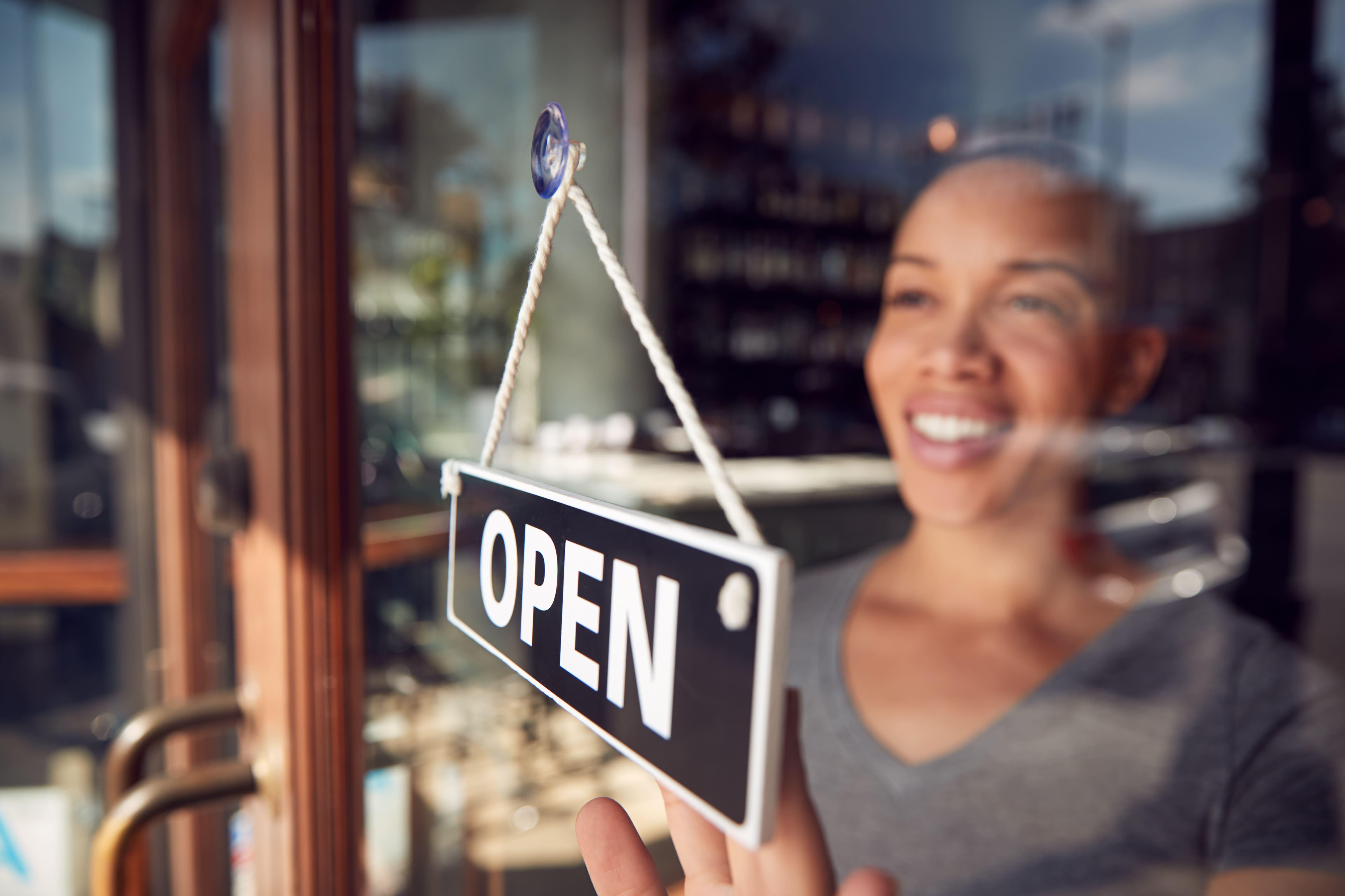 woman opening store - business insurance