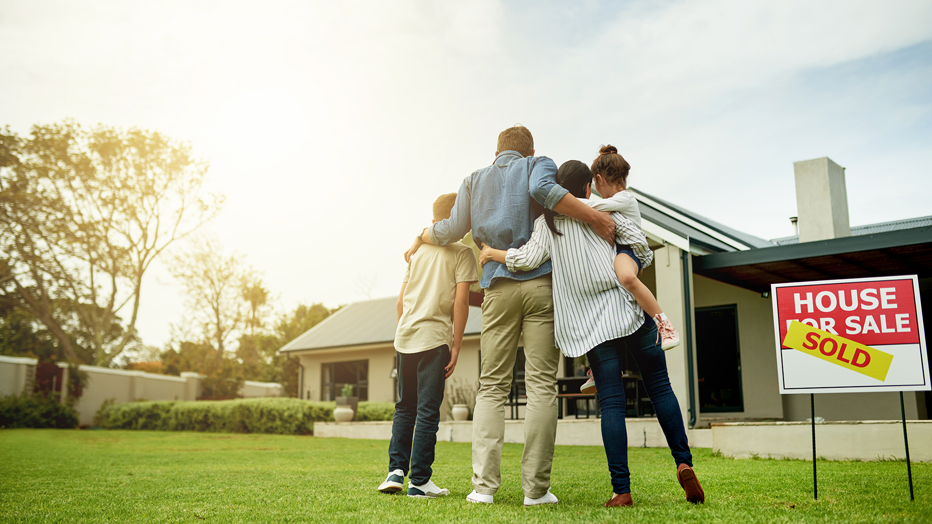 Family hugging in front of new home