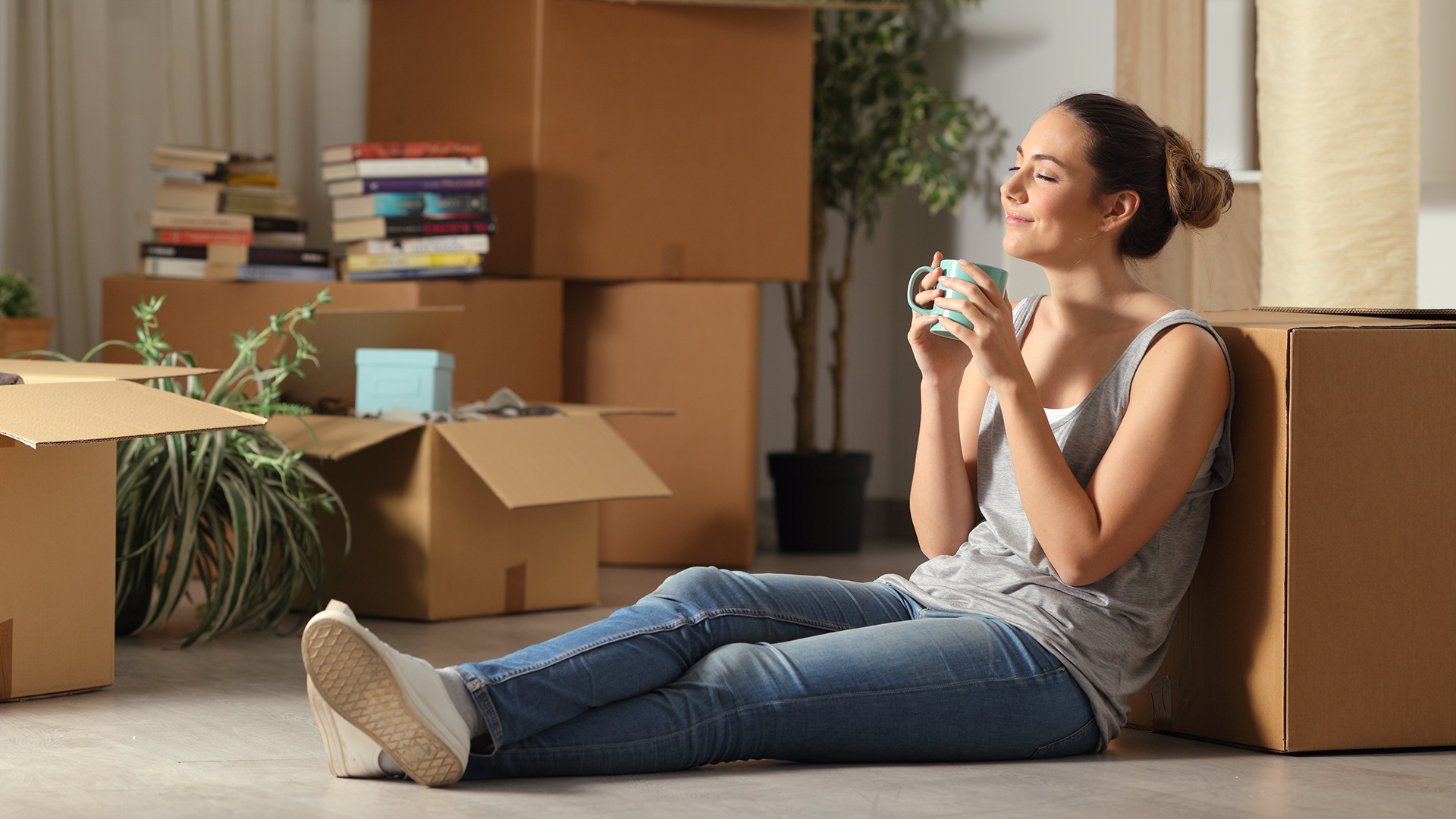 Woman sitting near moving boxes