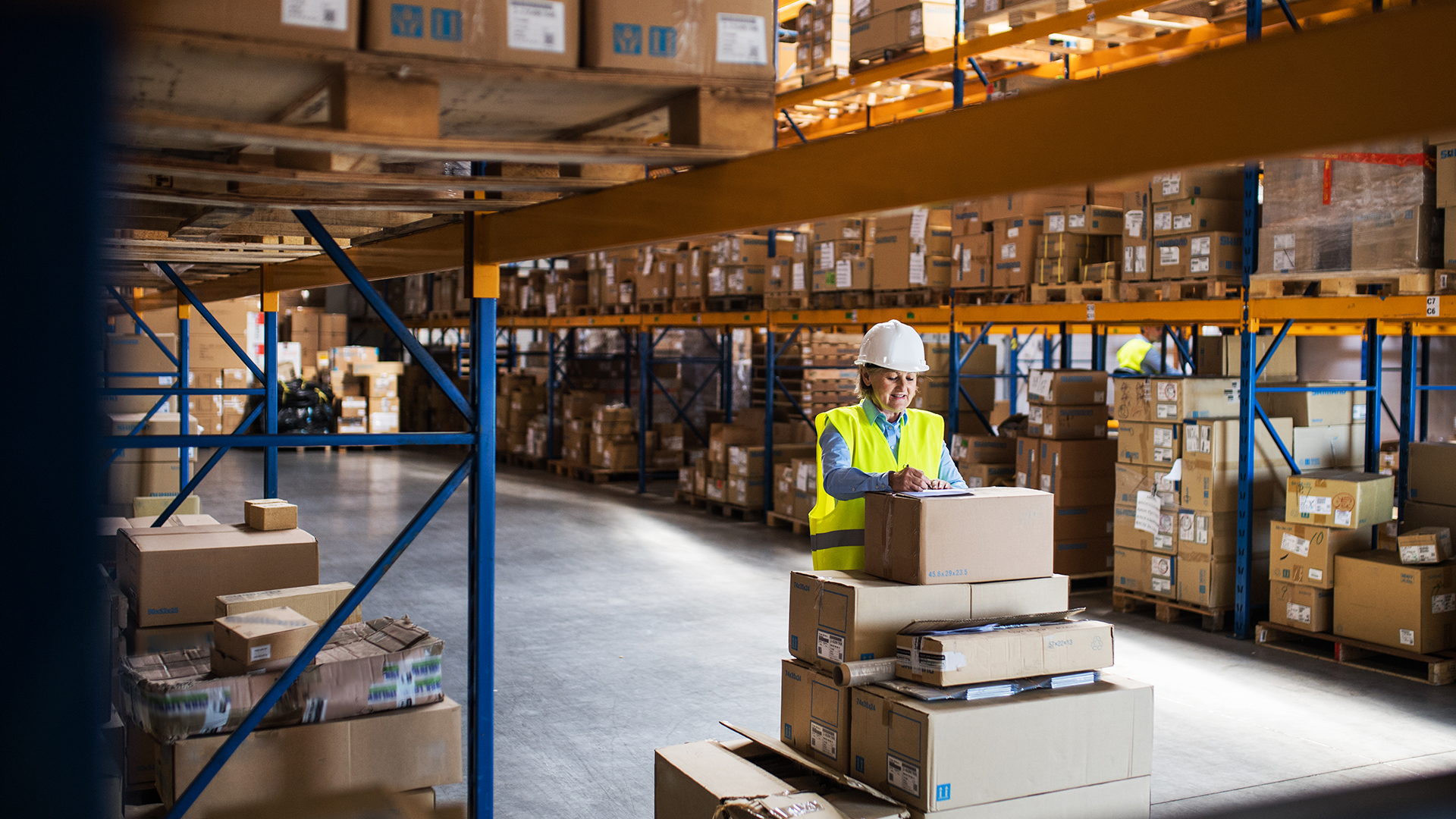 warehouse with packaged goods and shipping clerk in white hard hat